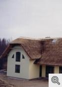 Dzīvojamās mājas ar niedru jumtu.